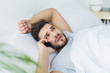 bearded man lying on bed and talking on smartphone in the morning