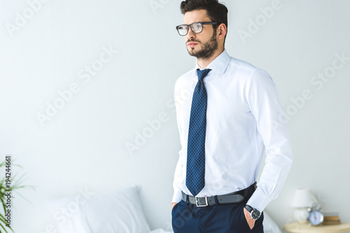 Obraz handsome businessman in white shirt and tie standing in bedroom - fototapety do salonu