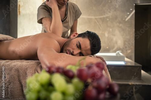 Photo Young man lying down during traditional acupressure procedure of Thai massage at