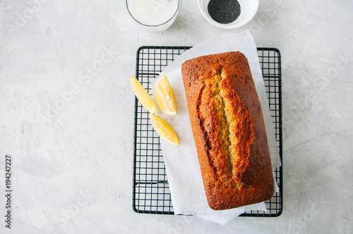 Plakat Domowej roboty cytryny makowego funta tort na drucianym stojaku. Biały kamień tło.