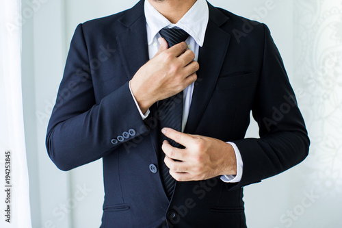 Fotografia  People, business,fashion and clothing concept - close up of man in shirt dressing up and adjusting tie on neck at home