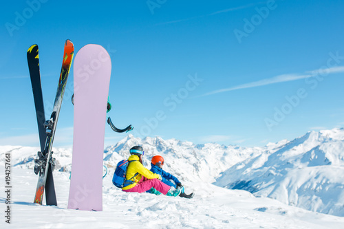 Printed kitchen splashbacks Purple Image of snowboard, ski on background of sitting sports couple on snowy hill in winter afternoon