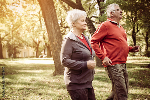 Foto  Cheerful seniors couple exercising in park.