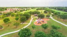 Aerial Urban Park With Playground And Asphalt Trails In Houston, Texas, America. Elevated View Of Slides And Swings In The Park Surrounded By Green Trees Near Notre Dame Church.