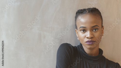 Serious attractive african woman with purple lipstick is looking in camera at isolated background Billede på lærred
