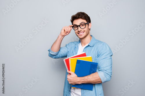 Fototapeta Portrait of cheerful, positive, smiling man with stubble in glasses, having three colorful copybooks in arm, holding eyelet of glasses on his face, looking at camera, isolated on grey background obraz