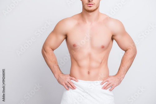 Cropped close up photo of shirtless sexy tempting muscular attractive man's torso, man is keeping hands on hips isolated on gray background copy-spac