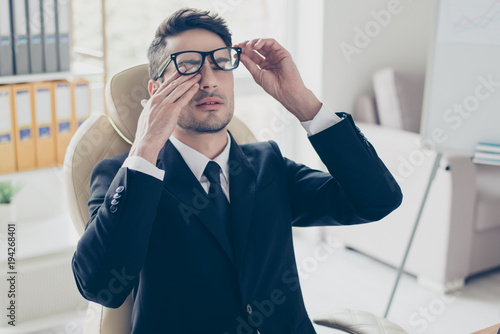 Health care healthcare people. Close up portrait of sad unhappy exhausted frustrated tired sleepy employee manager banker touching eyes holding glasses sitting at light modern office