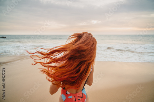 young red-haired woman with flying hair on the ocean coast at sunset, rear view Wallpaper Mural