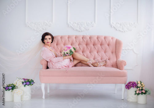 Fotografie, Obraz  Beautiful thoughtful bride lies in pink silk robe and veil on the luxury pink co