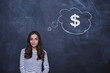 Happy confident woman standing in front of dollar sign written on a chalkboard. Concept of money management