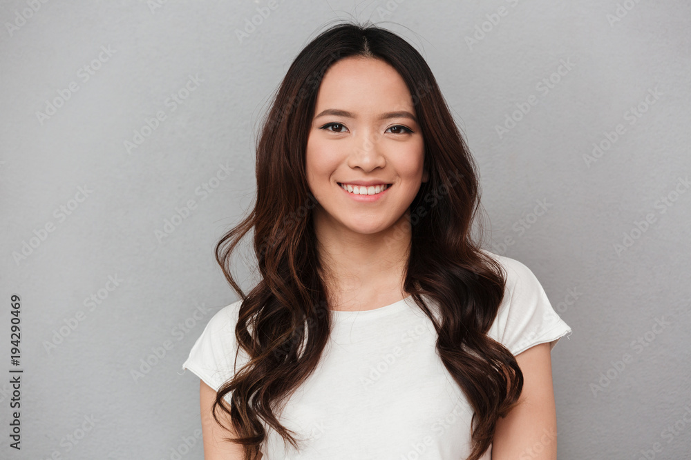 Fototapeta Portrait of asian lovely woman with dark curly hair posing with kind smile, isolated over gray background