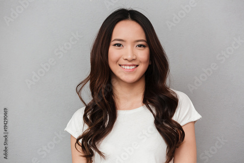 Carta da parati  Portrait of asian lovely woman with dark curly hair posing with kind smile, isol