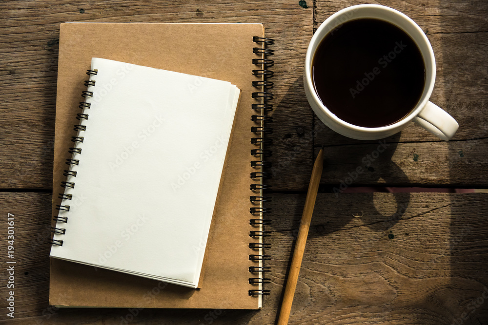 Fototapeta Top view of blank notebook with white coffee, laptop and with natural light on wooden table.
