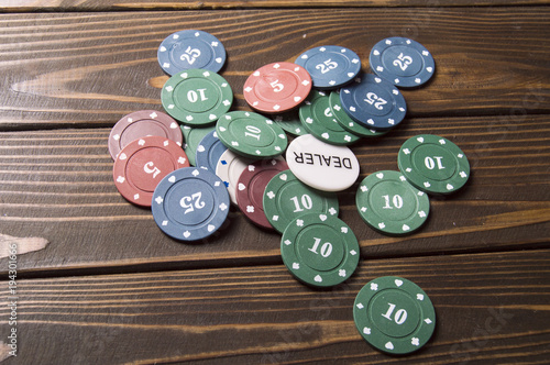 Stacks of poker chips on wooden table плакат