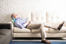 Middle Aged Man Taking A Nap On Couch