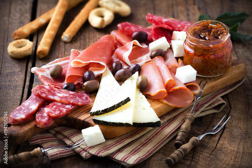 Fototapeta Cured meat and cheese platter of traditional Spanish tapas - chorizo, salsichon, jamon serrano, lomo and slices of goat cheese - served on wooden board with olives and bread sticks obraz