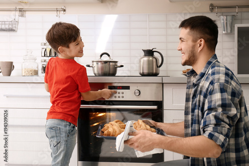 Poster Cuisine Young man and son baking croissants in oven indoors