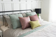 Modern furniture in a cozy minimalist bedroom with pastel pink and green accents pillows.