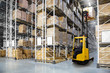 canvas print picture Huge distribution warehouse with high shelves and forklift with operator.