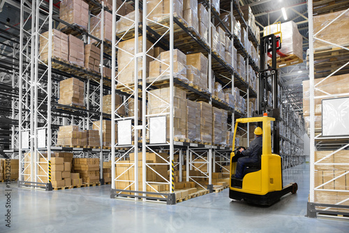 Staande foto Industrial geb. Huge distribution warehouse with high shelves and forklift with operator.