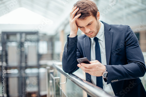 Serious man typing on smartphone  Sad man after breakup