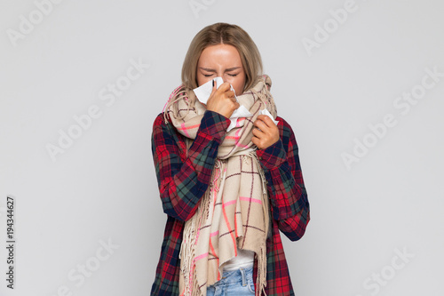 Leinwand Poster Young blonde Caucasian upset and sick woman sneezing or using handkerchieif to w