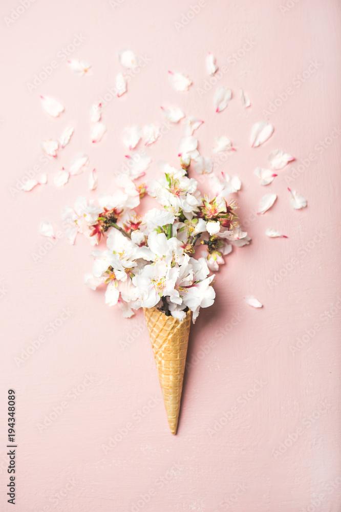 Leżał gofra słodki rożek z białymi migdałowymi kwiatami kwitnie nad pastelowym światłem - różowy tło, odgórny widok. Koncepcja nastroju na wiosnę lub lato