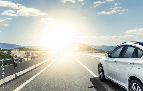 Photo  A white car rushing along a high-speed highway in the sun.