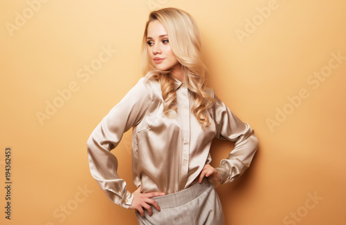 Photo Stylish business woman in blouse and pants posing on pink background