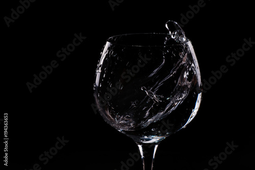 Water splashing out of a tall wine glass