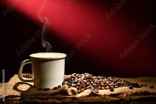 Poster Coffee bar Cup of coffee with smoke and coffee beans on reddish brown background