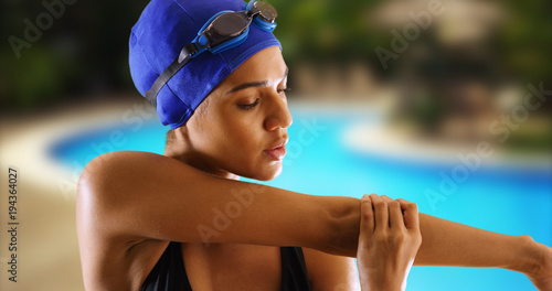 Fotografía Closeup of African swimmer stretching upper body by pool