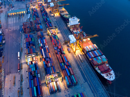Fotografia, Obraz  Container in import/export and business logistics,by crane,Trade port,Shipping cargo to harbor,Aerial view from drone,International transportation,Business logistics concept