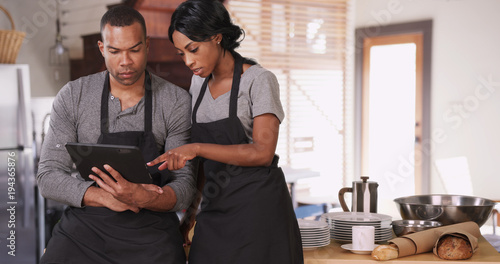 Photo  Small business owner showing employee new plan on tablet computer