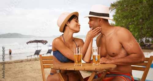 Fototapeta African American couple flirt while drinking at the beach