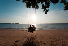 Couple In Love On A Swing Under A Tree On The Beach For Relax