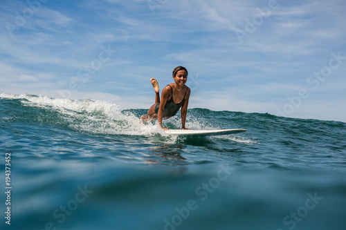 Poster Lieu connus d Asie Beautiful young indonesian woman in bikini surfing wave in Bali on the background of blue sky, clouds and tropical beach