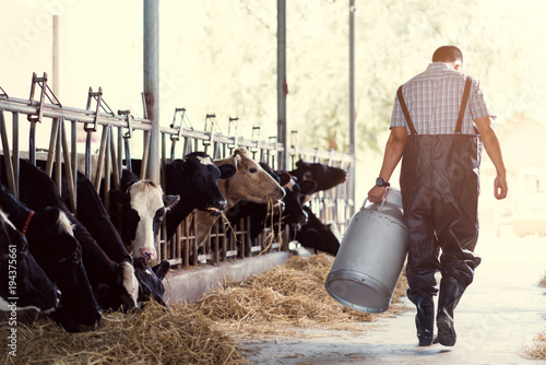 Fotografía  farmer asian are holding a container of milk on his farm