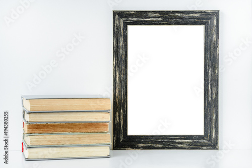 Empty Black Frame And Stack Of Old Books On White Background