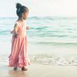 Beautiful little girl at the beach. Sunblock cream for children.