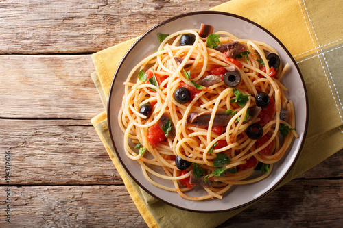 Traditional pasta alla puttanesca with anchovies, tomatoes, garlic and black olives close-up on a plate. horizontal top view