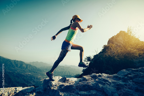 Fotografie, Obraz  young fitness woman trail runner running on the great wall top of mountain