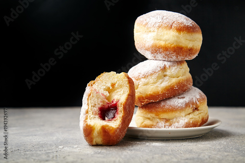 Fotografia A stack of three sufganiyot donuts with jelly on black background