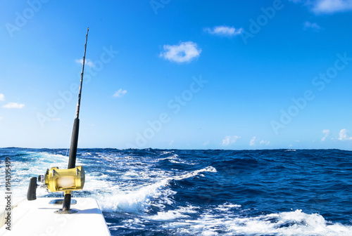 Poster Peche Fishing rod in a saltwater boat during fishery day in blue ocean. Successful fishing concept