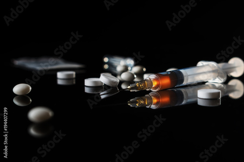 Different drugs - powder and pills and a syringe on a black background Slika na platnu