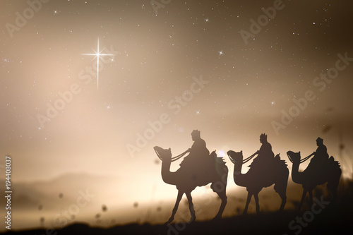 Canvas Print Christmas religious nativity concept: Prophecy magi and his friend with three camel on desert was going to bethlehem city in christmas eve