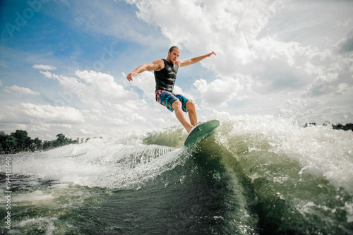Young and active man wakesurfing on the board down the river