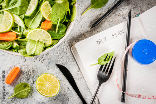 Diet plan weight lose concept, fresh vegetable salad with fork, knife, note pad, Fototapeta