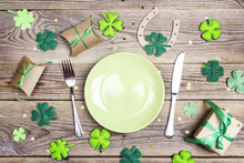 Festive Table Setting For St.Patrick's Day With Cutlery And Lucky Symbols On Wooden Table. Copy Space.